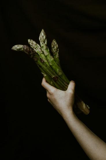 photo culinaire produit brut asperges dans la main clair obscur